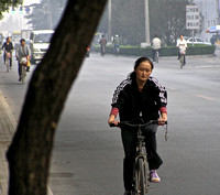Woman on bicycle, early morning Bejing China